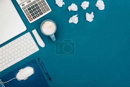 Photo for Top view of crumpled papers, calculator and digital devices on blue - Royalty Free Image