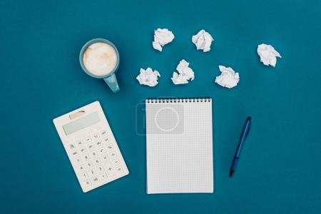 top view of blank notebook with pen, calculator and crumpled papers on blue