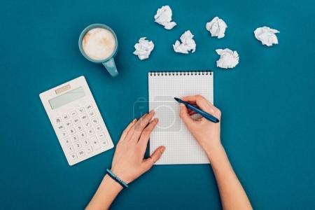 Photo pour Plan recadré de la personne écrivant dans un carnet sur le lieu de travail sur bleu - image libre de droit