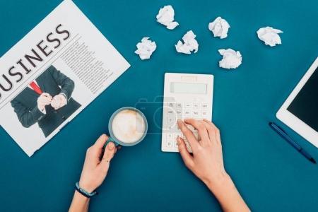 Photo pour Plan recadré de la personne en utilisant une calculatrice et boire du café sur bleu - image libre de droit