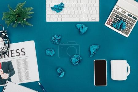 Photo for Top view of crumpled papers, computer keyboard, calculator and smartphone on blue - Royalty Free Image