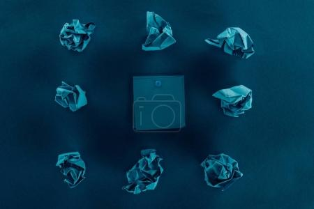 top view of crumpled papers and blank notes on blue