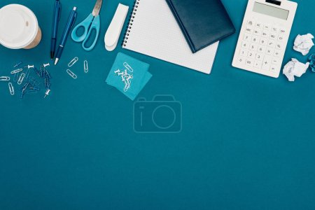 top view of calculator, coffee to go and office supplies on blue