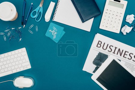 Photo for Top view of business newspaper, digital tablet, calculator and office supplies on blue - Royalty Free Image