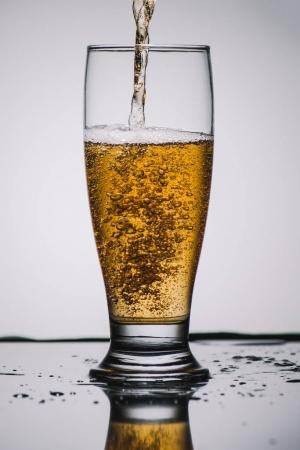 pouring light beer into transparent glass