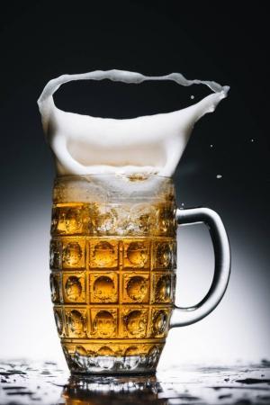 splashing foam of pint of golden fresh beer