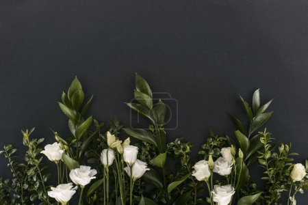 top view of eustoma flowers and branches over black background
