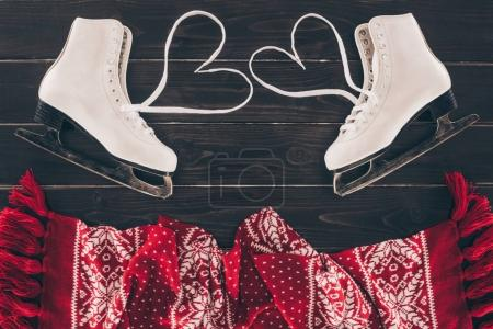 top view of white skates with hearts shaped shoelaces and scarf on tabletop
