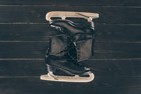 top view of pair of black skates on dark table