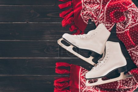 Photo for Top view of pair of white skates and red scarf on wooden table - Royalty Free Image
