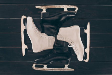 top view of pairs of white and black skates on wooden surface