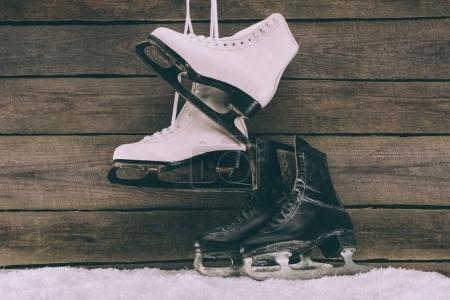 pairs of white and black skates near wooden wall
