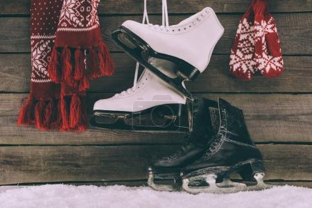 red scarf with gloves and white and black skates