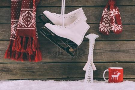 red scarf with gloves and white skates hanging on striped wall