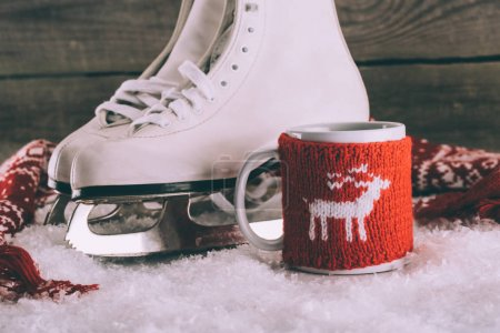pair of white skates with cup with knitted ornament and scarf