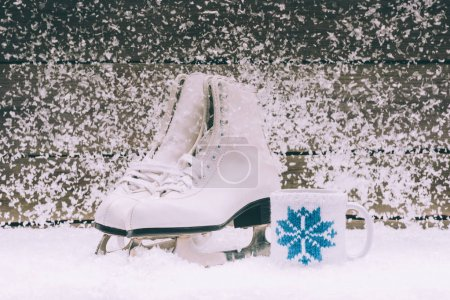 pair of white skates with cup on snow