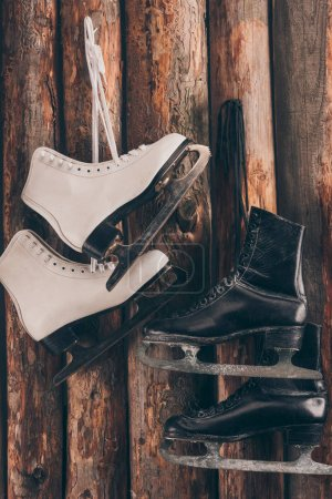 pairs of white and black skates hanging on wooden wall