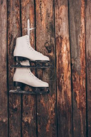 pair of white skates hanging on wooden shabby wall