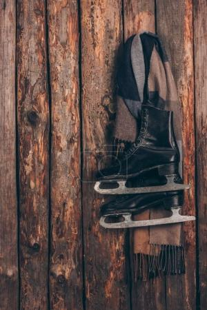 warm scarf with pair of black skates hanging on wooden wall