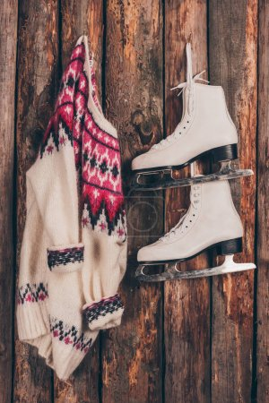 warm sweater and pair of white skates hanging on wooden wall