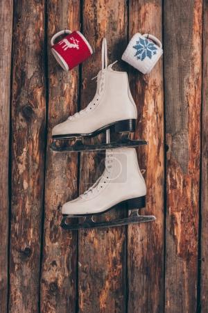 two cups and pair of white skates hanging on wooden wall