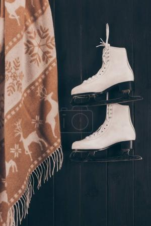 pair of white skates and scarf hanging on wall