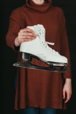 cropped image of woman in holding pair of white skates isolated on black