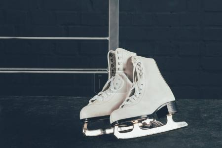 pair of white figure skates on gray floor