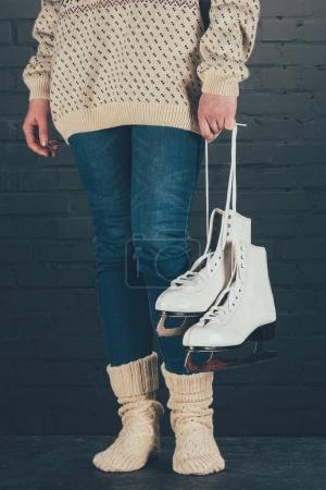 cropped image of woman standing and holding skates with shoelaces