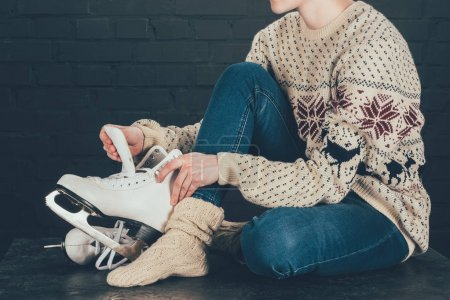 cropped image of woman sitting on gray floor and wearing white skates