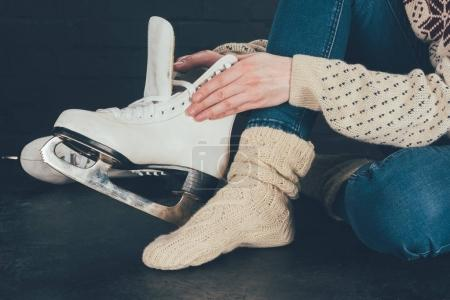 cropped image of woman sitting and wearing white skates