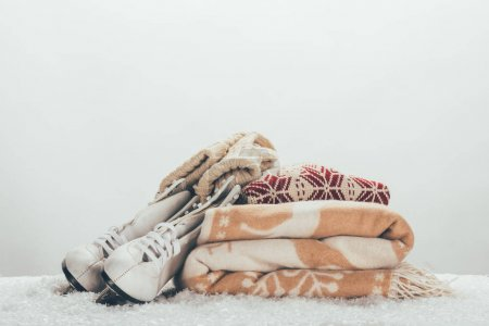 white skates with stack of blanket and sweater on snow