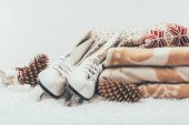 white skates with pine cones and stack of blanket and sweater