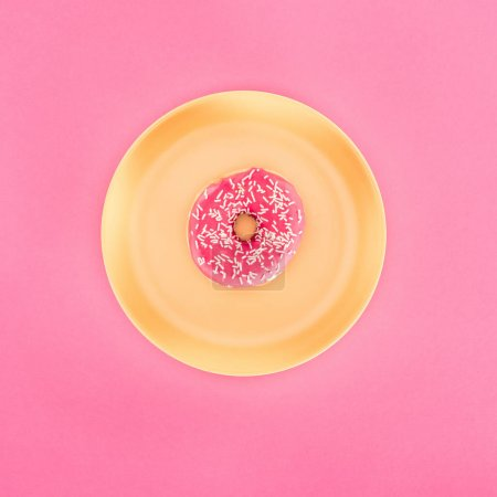 top view of pink glazed doughnut on yellow plate isolated on pink
