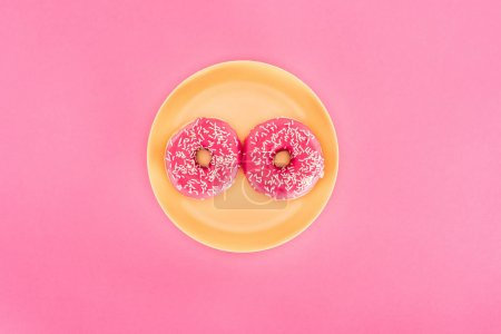 top view of pink glazed doughnuts on yellow plate isolated on pink