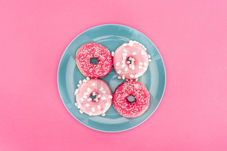Photo for Top view of glazed doughnuts on plate isolated on pink - Royalty Free Image