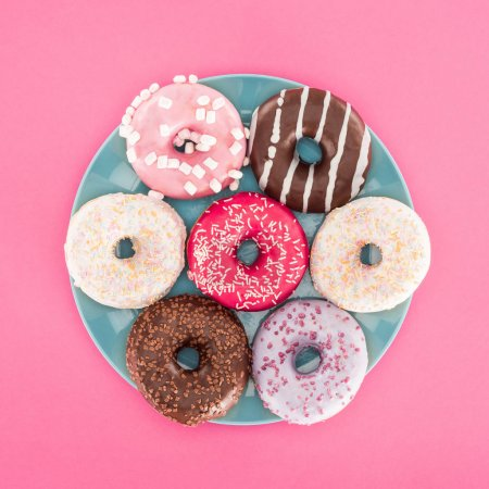 top view of various glazed doughnuts on plate isolated on pink