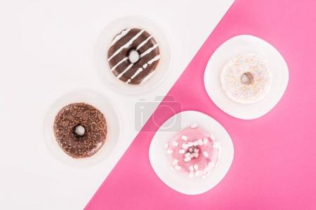 top view of various tasty doughnuts on plates