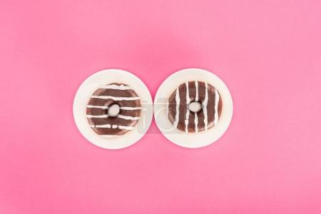 top view of doughnuts glazed with chocolate on plates isolated on pink