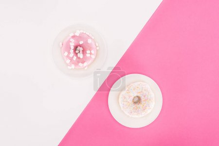 top view of various glazed doughnuts on plated on white and pink surface