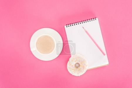 top view of glazed doughnut with cup of coffee and blank notebook