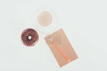 top view of doughnut with cup of coffee and blank kraft paper on white tabletop