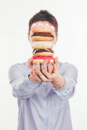 woman holding stack of doughnuts in front of face isolated on white