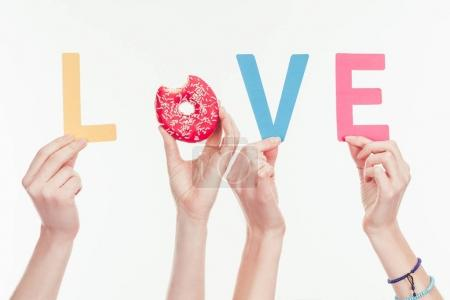 cropped shot of women assembling love word with colorful letters and bitten doughnut