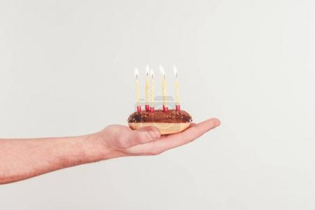 cropped shot of woman holding doughnut with birthday candle