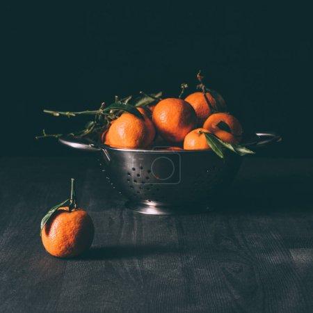 Photo pour Bouchent la vue des tas de mandarines aux feuilles dans la crépine sur une table en bois foncée - image libre de droit