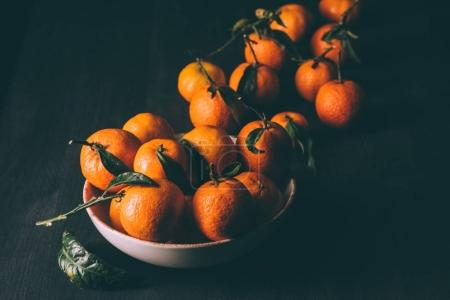 close up view of mandarins in bowl on dark wooden tabletop