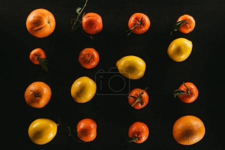 flat lay with ripe lemons and tangerines isolated on black