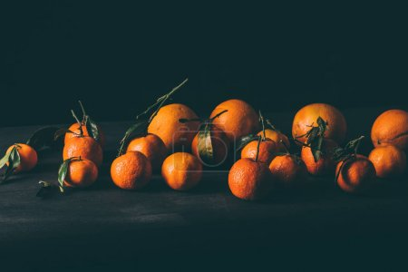 close up view of ripe mandarins with leaves on wooden tabletop