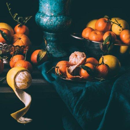 Nahaufnahme der Anordnung von frischen Zitronen und Mandarinen in Schüssel und Sieb auf dem Tisch mit dunkler Tischdecke